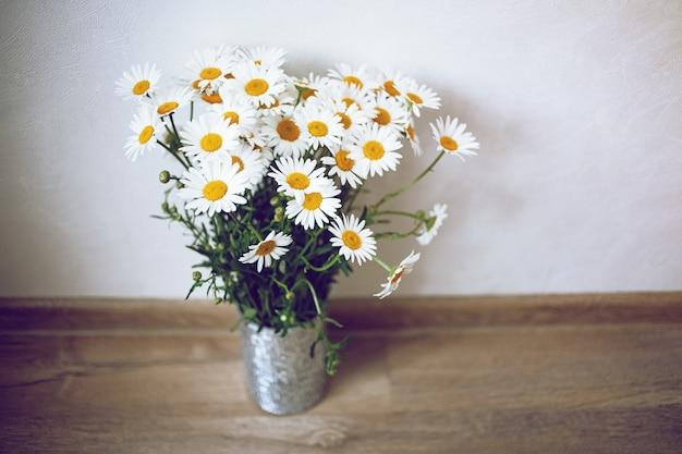 Leuke zilveren vaas met witte chamomiles in lichte kamer en houten vloer. shabby chic stijl.