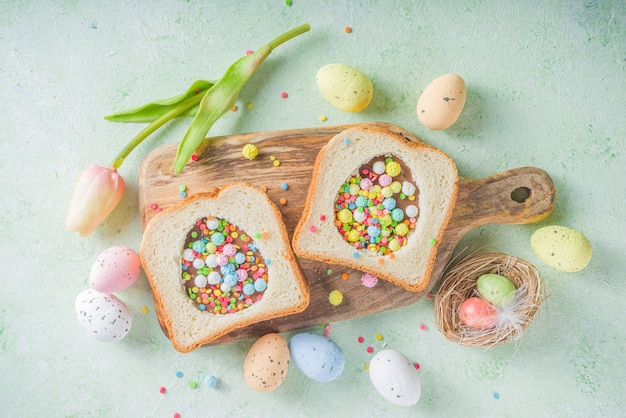 Leuke zoete ontbijtsandwich. creatief idee voor paassnack of lunch. toast sandwich met pindakaas en chocolade pasta, met kleurrijke hagelslag bovenaanzicht.