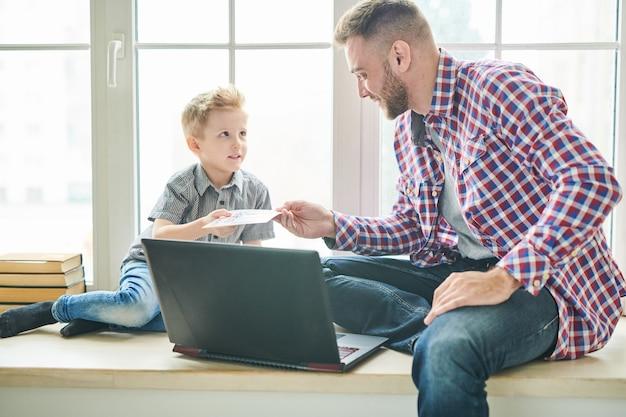 Leuke zoon die de kaart van de vaderdag geeft aan papa