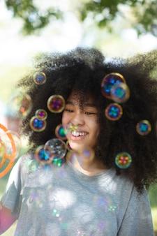 Leuke zwarte tiener die met zeepbellen speelt