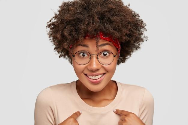 Leuke zwarte vrouw lacht vrolijk, voelt trots op haar daden, vraagt iets, is verbaasd dat ze werd uitgekozen, heeft een krullend kapsel, modellen tegen een witte muur, overweldigd door positieve emoties