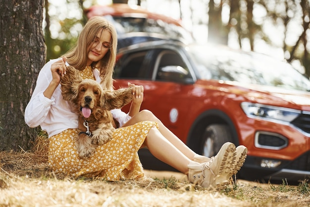 Leunend op de boom. vrouw met haar hond buiten in het bos tegen auto's hebben veel plezier.