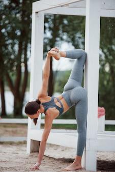 Leunend op houten constructie. brunette met mooie lichaamsvorm in sportieve kleding heeft fitnessdag op een strand
