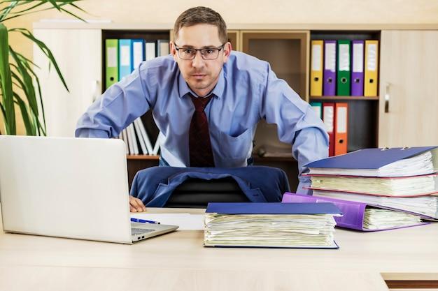 Leunt met zijn handen op de tafel inspannend kantoorwerk voorbereiding van het rapport