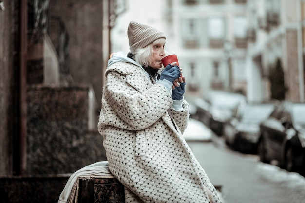 Leven in armoede. arme senior vrouw die thee drinkt terwijl ze op straat zit