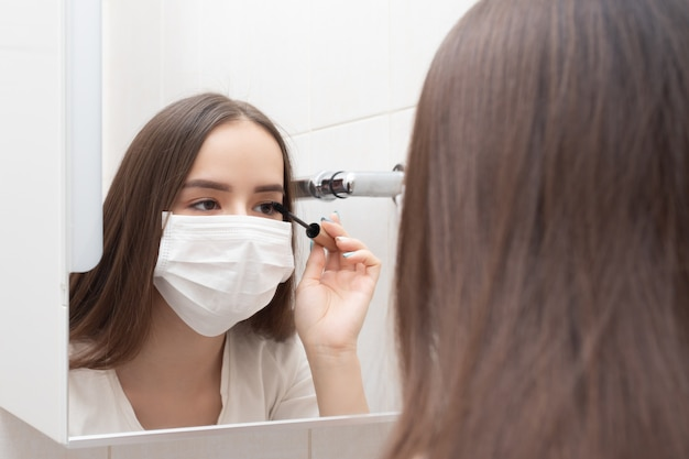 Leven in quarantaine van een coronovirus. een vrouw met een medisch masker doet make-up, mascara's haar ogen. ziektepreventie en -bescherming
