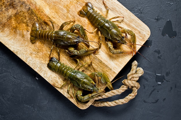 Levende rivierkreeften rennen weg van de houten snijplank.