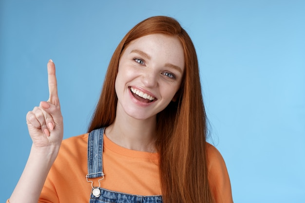 Levendig actief energiek blij lachend hepful roodharige vrouwelijke collega toont je geweldige promo wijzende wijsvinger omhoog grijnzend introduceren cool product aanbevelen uitproberen blauwe achtergrond