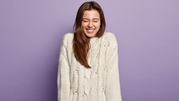 Levendig dolgelukkig meisje met stralende glimlach, lacht van plezier, heeft witte tanden, gekleed in trui met lange mouwen, sluit ogen, heeft donker haar, modellen over paarse muur. positieve emoties