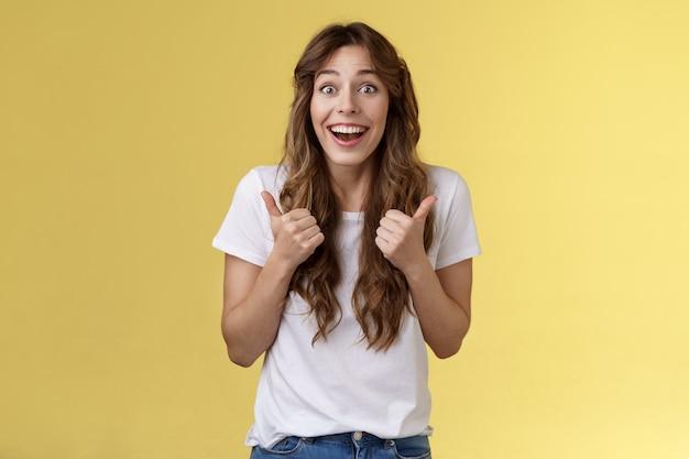 Levendig opgewonden blij schattig europees meisje ondersteunend geef positief antwoord denk evenement geweldig glimlachend in het algemeen duimen omhoog goedkeuring tonen, geweldige keuze accepteren staan gele achtergrond opgewonden.