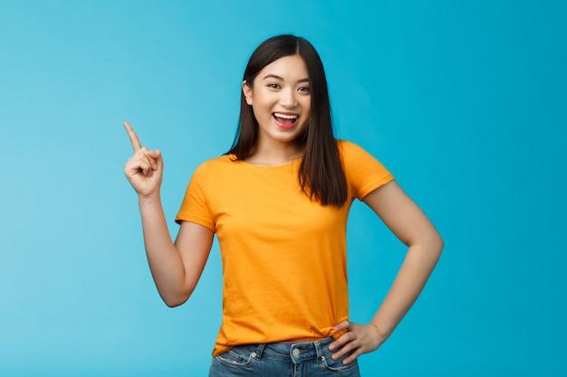 Levendig schattig vriendelijk ogend aziatisch meisje met donker kort haar dat de weg wijst naar de linkerbovenhoek en opgetogen grijnst, richting geeft, nieuw product introduceert, vrolijk glimlachend tevreden.