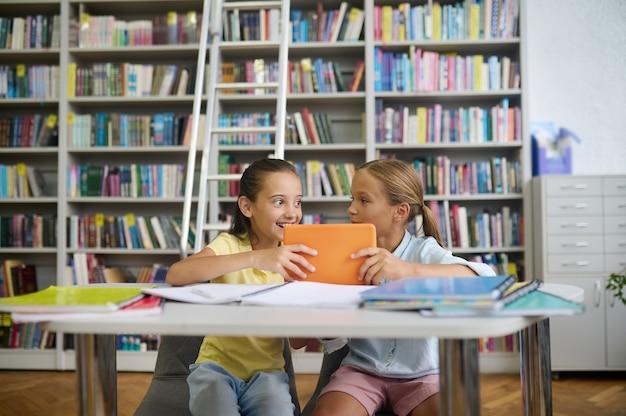 Levendig schoolmeisje en haar peinzende klasgenoot in een openbare bibliotheek