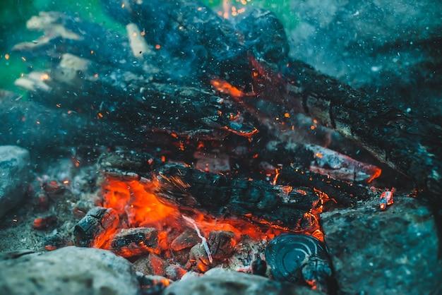 Levendig smeulend brandhout verbrand in close-up in vuur. oranje vlam van kampvuur. volledig beeld van vreugdevuur. warme wervelwind van gloeiende sintels en as in de lucht. vonken in bokeh