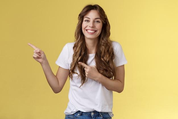Levendig verrast gelukkig vrolijk lachend gelukkig meisje lang krullend kapsel grijnzend toothy witte perfecte grijns wijsvinger links zijwaarts bespreken nieuwe meubels verhuizen in appartement toon vrienden