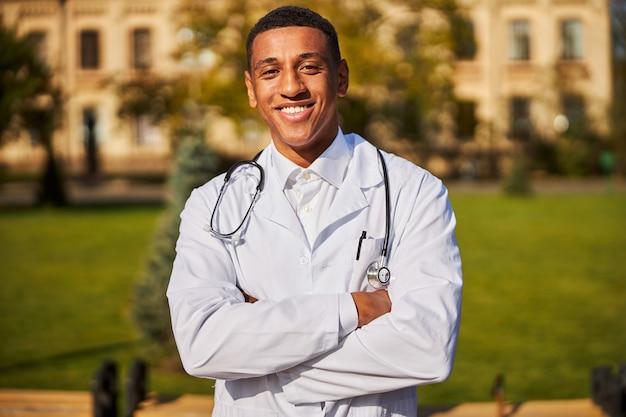Levendige arts zonder masker die zijn armen over elkaar slaat op de binnenplaats van een ziekenhuis