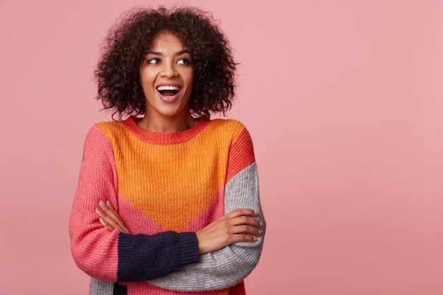 Levendige charismatische aantrekkelijke afro-amerikaan met een afro kapsel met opwinding kijkt links naar de lege ruimte, lacht, ha-ha, sta met gekruiste armen, kleurrijke trui dragen, geïsoleerd op roze