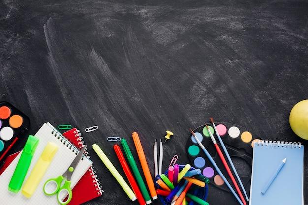 Levendige creatieve briefpapier en -laptops op een grijze achtergrond