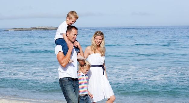 Levendige familie die op het zand loopt