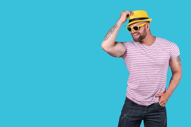 Levendige jonge, bebaarde man in felblauwe hemdjeans en gele stijlvolle hoedzonnebril die in z...