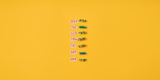 Levendige kleurrijke plat leggen van geneeskunde pil capsules gevuld met kandijsuiker hagelslag op gele achtergrond. creatief concept van overdosis medicijngebruik en verslaving aan voedingssupplement. banier.