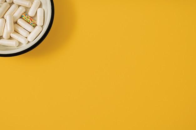 Levendige kleurrijke plat leggen van geneeskunde pil capsules gevuld met kandijsuiker hagelslag op gele achtergrond. creatief concept van overdosis medicijngebruik en verslaving aan voedingssupplement.