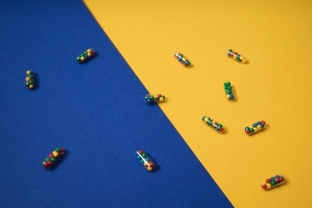 Levendige kleurrijke plat leggen van geneeskunde pil capsules gevuld met kandijsuiker hagelslag op gele en blauwe achtergrond. creatief concept van overdosis medicijngebruik en verslaving aan voedingssupplement.