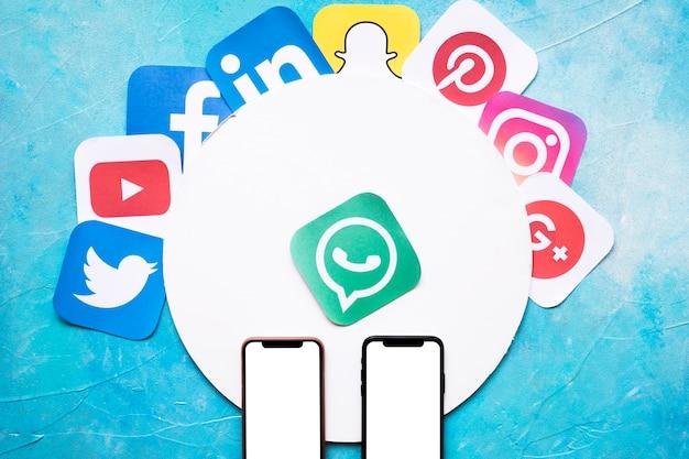 Levendige netwerken applicatie pictogrammen met twee mobiele telefoon op blauwe muur