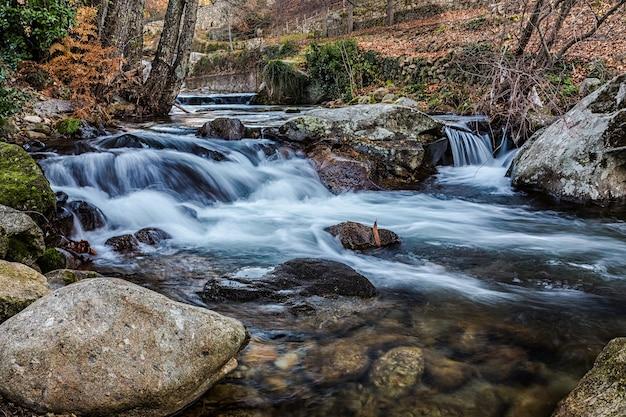 Levendige omgeving van een rivier die over rotsen met lange blootstelling stroomt
