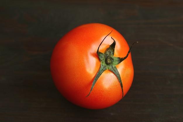 Levendige rode tomaat geïsoleerd op zwart