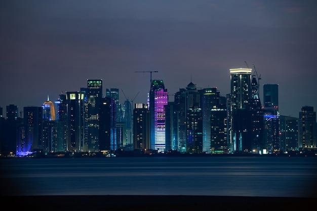 Levendige skyline van doha at night, gezien vanaf de andere kant van de zonsondergang van de hoofdstad baai.