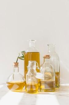 Levendige transparante olieflessen op marmeren vloer tegen de witte muur