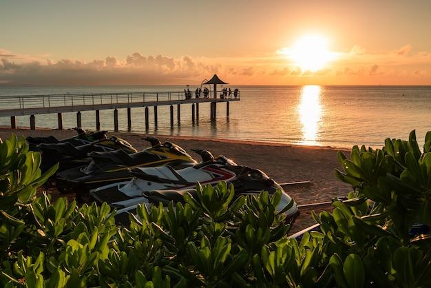 Levendige zonsondergang die waterscooters op strandzand verlicht. kustplanten op de voorgrond en toeristen op de pier.