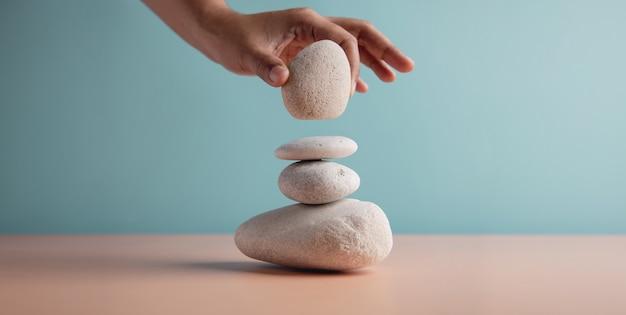 Levensbalansconcept. hand instelling witte natuurlijke zen stone stack. balanceren van geest, ziel en geest. mentale meditatie oefening