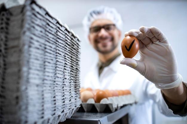 Levensmiddelentechnoloog die bij de industriële eiersorteermachine staat en een ei vasthoudt dat de kwaliteitscontroletest heeft doorstaan.