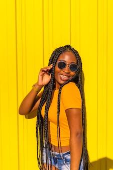 Levensstijl, aantrekkelijk zwart meisje met lange vlechten, gele t-shirts en korte spijkerbroek op een gele muur. met zonnebril in de stadssessie in de stad, trap danseres, kusjes in de lucht blazen