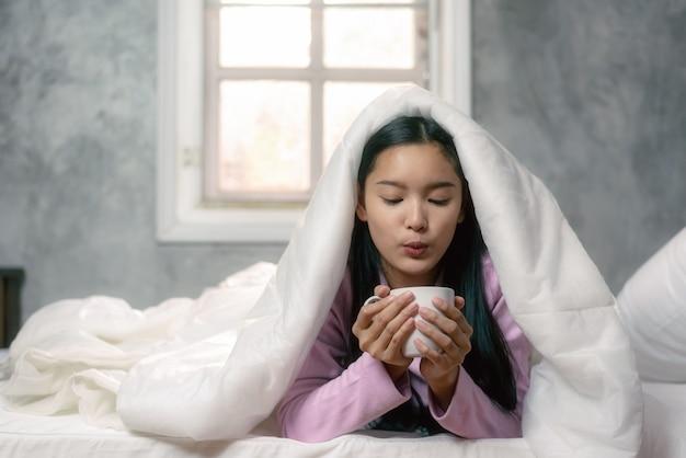 Levensstijl aziatische vrouw in slaapkamer koffie drinken na het ontwaken in de ochtend