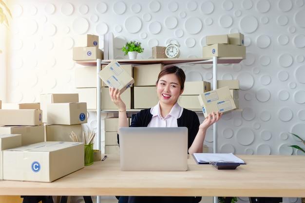 Levensstijl bedrijfsvrouwenzitting in bureau die het schermlaptop glimlach het werken kijken