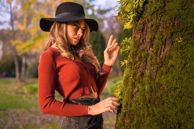 Levensstijl blond kaukasisch meisje in een rode trui en een zwarte hoed genieten van de natuur in een park met bomen in het mooie herfstportret van de jonge vrouw naast een boom met mos