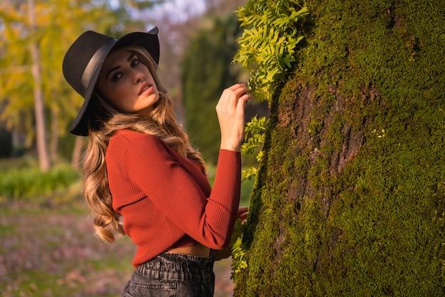 Levensstijl blond kaukasisch meisje met een rode trui en een zwarte hoed genieten van de natuur in een park met bomen portret van de jonge vrouw naast een prachtige boom in de herfst met mos