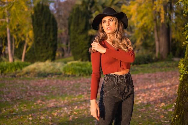 Levensstijl blonde blanke meisje in een rode trui en zwarte hoed genieten van de natuur in een park met bomen portret van de jonge vrouw genieten van de herfstzon