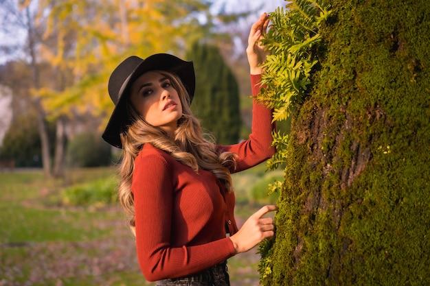 Levensstijl blonde kaukasische meisje in een rode trui en een zwarte hoed genieten van de natuur in een park met bomen portret van de jonge vrouw kijken naar de prachtige boom met mos in de herfst