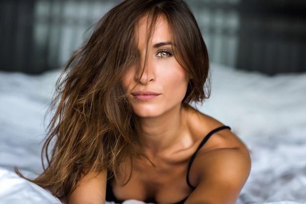 Levensstijl close-up portret van prachtige mooie brunette vrouw, perfecte huid, natuurlijke make-up, olijfkleurige ogen, gebruinde huid, zachte pastelkleur, ontspannen in haar bar, lingerie dragen, ochtendtijd.
