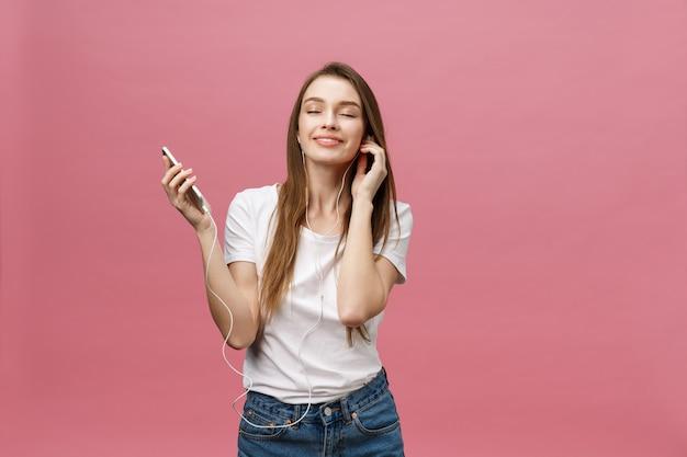 Levensstijl concept. jonge vrouw met behulp van de telefoon voor het luisteren naar muziek op roze achtergrond