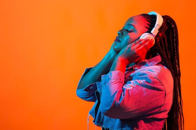 Levensstijl concept - portret van mooie afrikaanse amerikaanse vrouw vreugdevolle luisteren naar muziek.