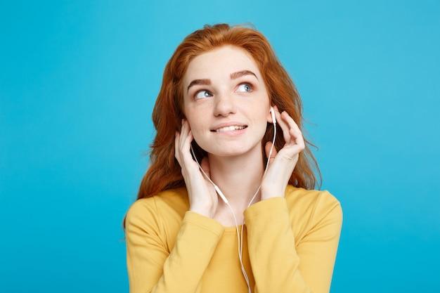 Levensstijl concept portret van vrolijk gelukkig gember rood haar meisje geniet van het luisteren naar muziek met koptelefoon blij lachend geïsoleerd op blauwe pastel muur kopie ruimte