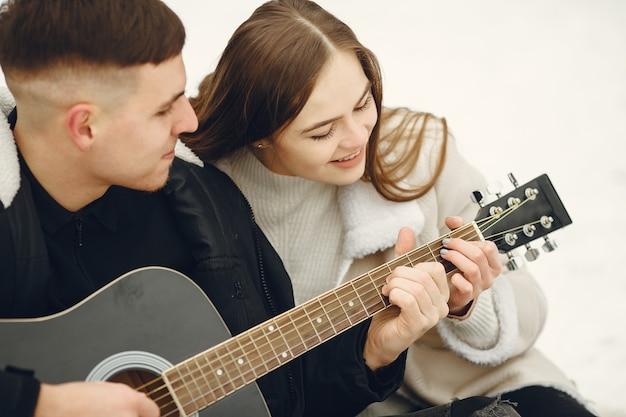 Levensstijl die van paar zit in besneeuwd bos is ontsproten. mensen besteden wintervakantie buitenshuis. echtpaar met een gitaar.