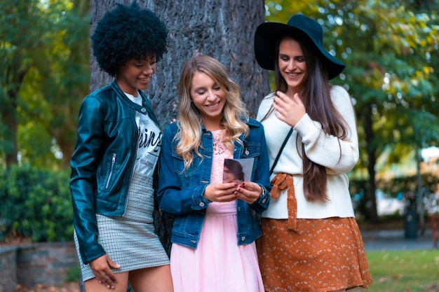 Levensstijl. drie goede vrienden in een herfstsessie in een boom, een blondine, een brunette en een latijns meisje met afrohaar