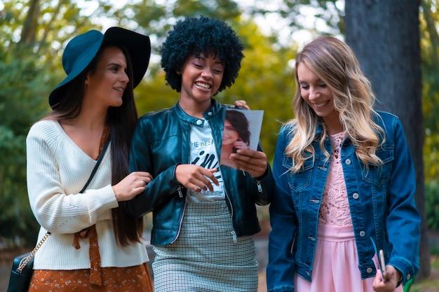 Levensstijl. drie goede vrienden in een park, een blondine, een brunette en een latijns meisje met afrohaar