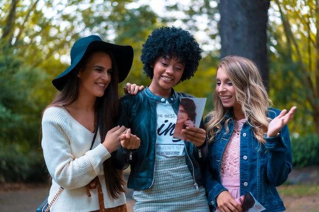 Levensstijl. drie goede vrienden in een park met plezier, een blondine, een brunette en een latijns meisje met afrohaar