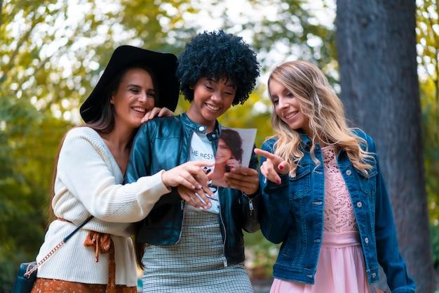 Levensstijl. drie jonge vrienden die een park bezoeken, een blondine, een brunette en een latijns meisje met afrohaar